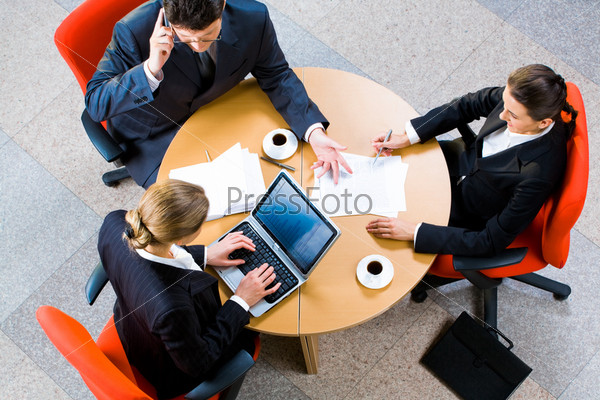 Portrait of three business person sitting at the round table