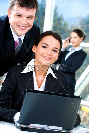 Portrait of two business people looking at camera together indoor