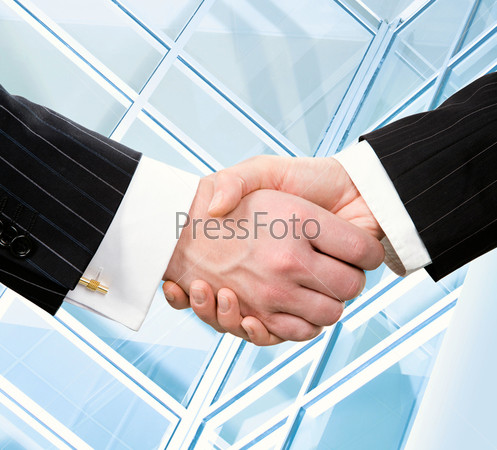 Handshake of businesspeople on the background the modern window
