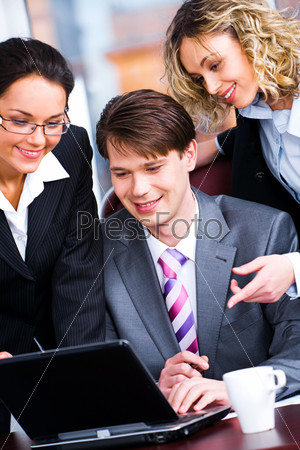 Business people gathered together looking at monitor of laptop