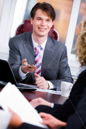 Portrait of boss sitting at the table and talking something at meeting