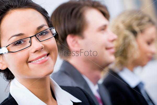 Лицо умной женщины в очках на фоне людей