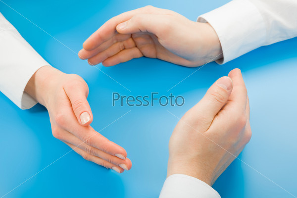 Human hands making symbolic circle on a blue background
