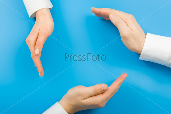 Conceptual circle made from human hands on a blue background