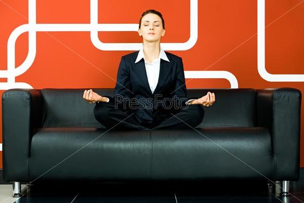 Деловая женщина медитирует на диване в кабинете