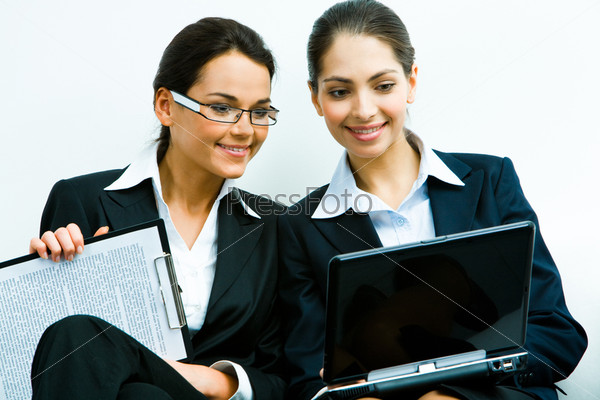 Portrait of two confident women in suits looking at the screen of a laptop with smiles