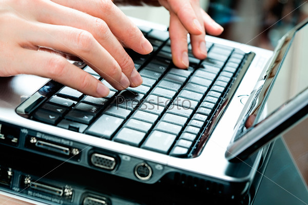 up of businesswoman's hands on the keys of laptop