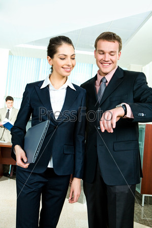 Portrait of a young  businessman looking at his watch with his  partner near by