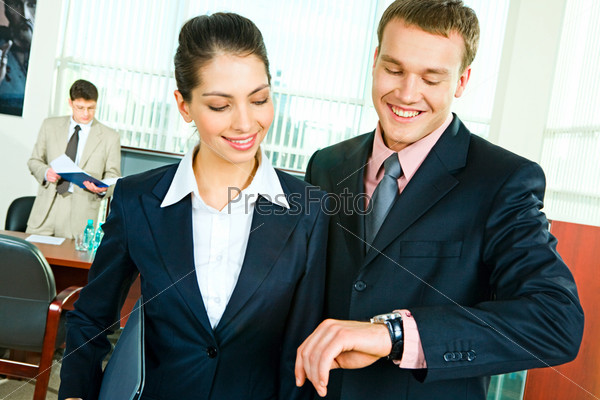 Two colleagues looking attentively at businessman's watch in the office with smiles