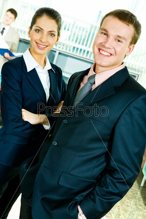 Portrait of confident business lady and her colleague looking at camera