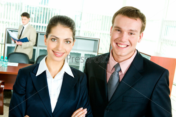 Photo of happy business partners looking at camera in the office