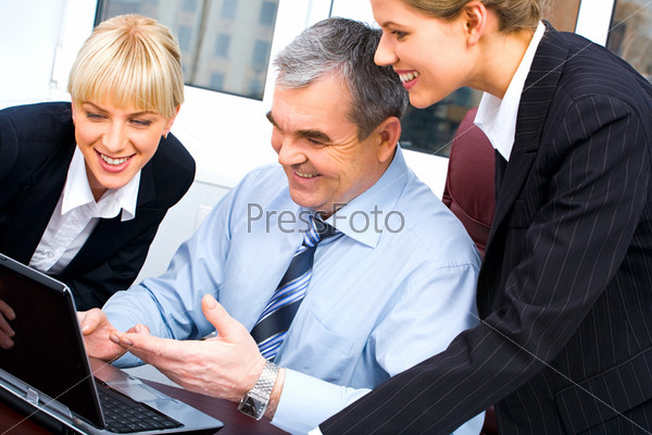 Photo of  boss pointing at laptop screen and showing something to his  colleagues