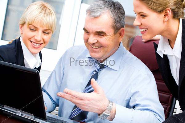 Фотография на тему Пожилой босс и две молодые женщины смотрят на монитор ноутбука