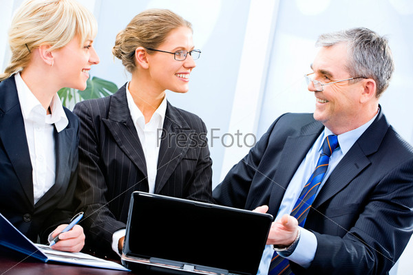 Portrait of three businesspeople sitting near laptop and discussing working ideas
