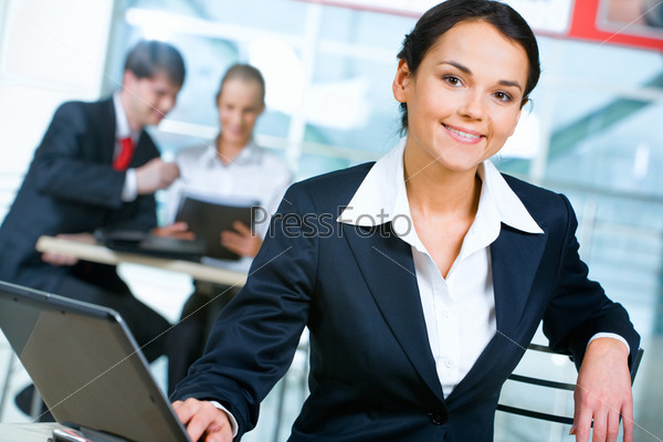 Portrait of confident businesswoman sitting near table with laptop on it