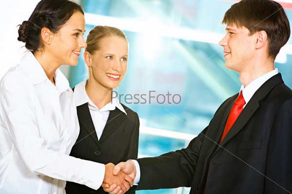 Photo of two business partners shaking hands after signing contract in the office