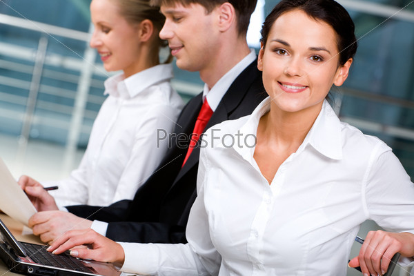 Photo of smiling business lady on the background of two working business partners