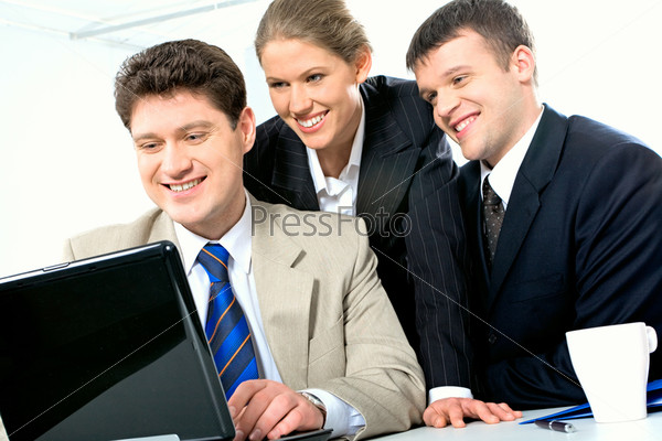 Portrait of three confident business partners looking at the laptop monitor in the office