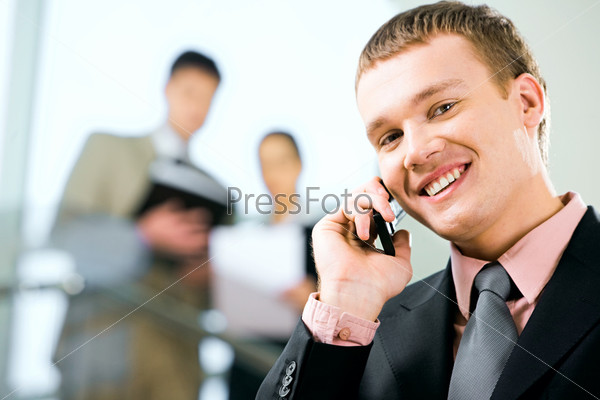 Portrait of a young handsome businessman speaking on the phone
