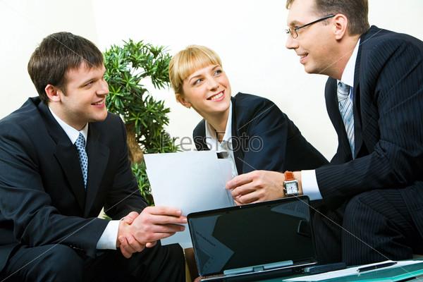 Бизнесмен передает документы деловому партнеру на встрече