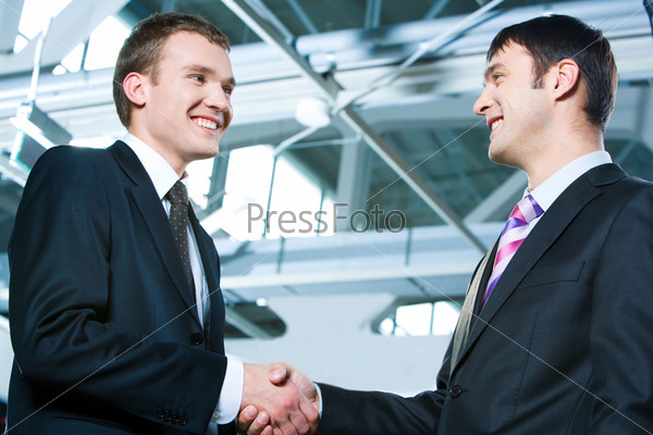 Portrait of two confident business men shaking hands at meeting