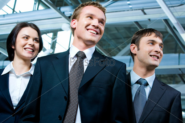 Portrait of strong business team standing next to each other and looking aside