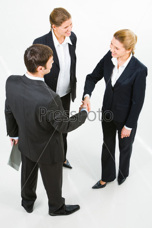 Image of successful partners shaking hands in the white room