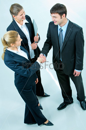 Image of people making a business agreement and standing in the room