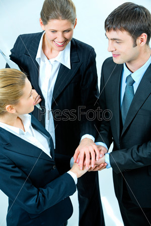 Image of business people putting their hands on the top of pile
