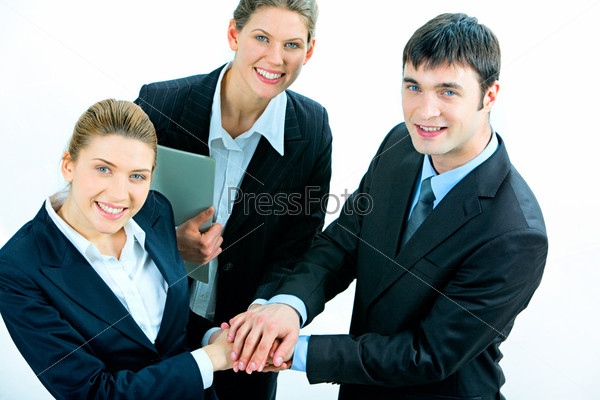 Image of business people putting their hands on top of pile and looking at camera