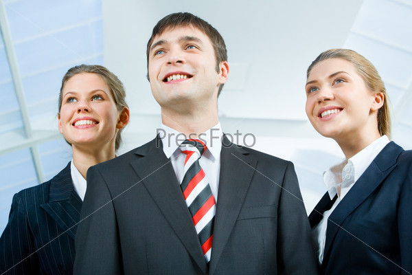 Image of three business people in suits and smiling