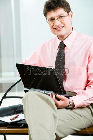 Преуспевающий менеджер сидит на скамейке с ноутбуком в руках
