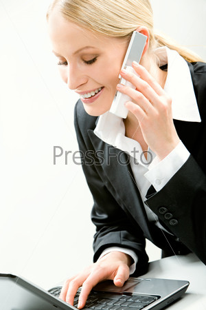 Portrait of attractive business woman typing on the laptop and calling on the mobile