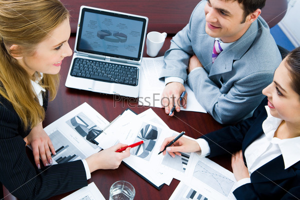Image of business woman explaining and pointing to her project to colleagues