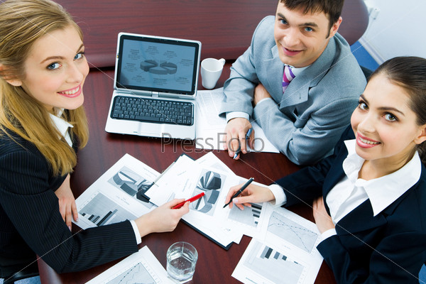 Portrait of three employees looking at camera during business briefing