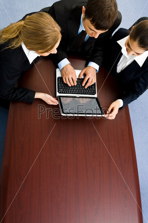 Business team of three people gathered together round table  and working