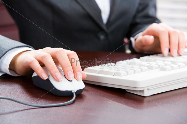 Business woman's hands touching computer mouse and white keyboard