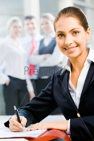 Young successful smiling woman sitting at the table and looking at camera in a working environment
