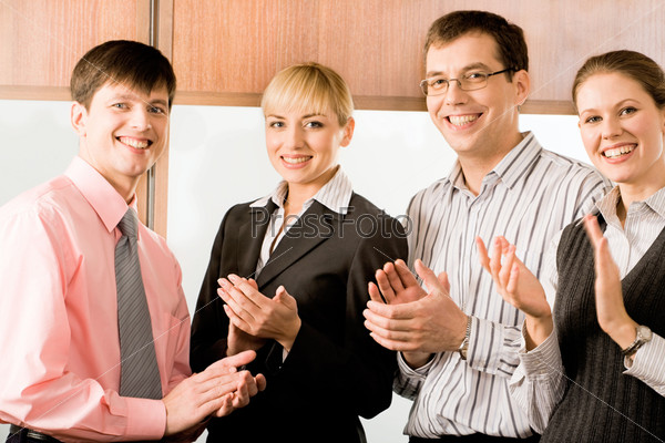 Portrait of four business people smiling and applauding in the office