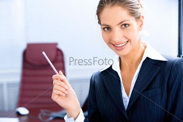 Портрет деловой женщины, держащей ручку, в рабочей обстановке