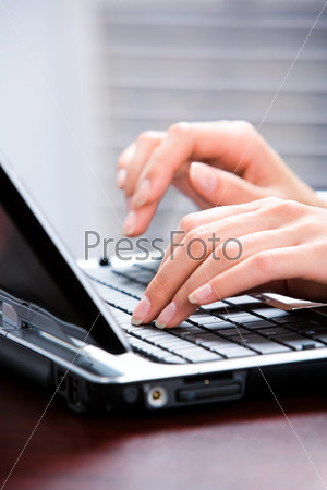 Image of hands typing a letter on the keyboard of laptop