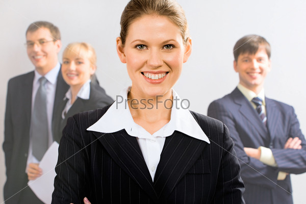 Portrait of attractive leader with her business team in the background