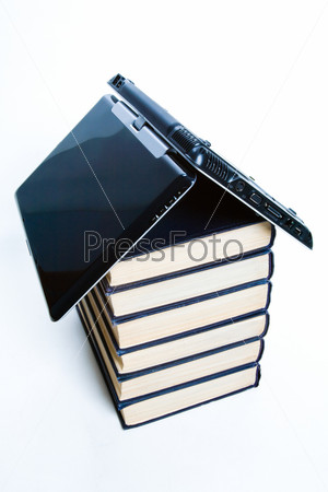 Symbol of house: stack of books with a black laptop on top