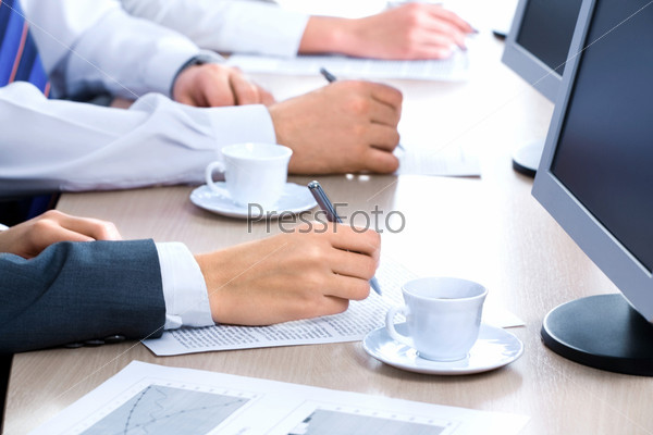 Hands of three business people over the documents lying on the table with cups and monitors near by
