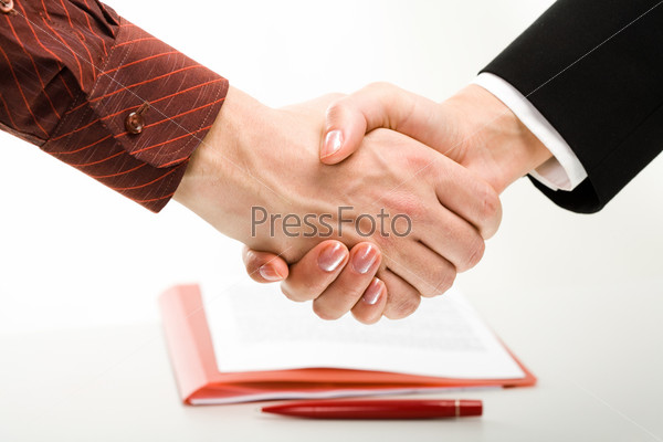 Image of two business people's handshake after making an agreement on the background of contract and red pen