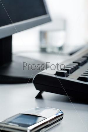 Фото телефона, лежащего на столе, рядом с монитором, клавиатурой и стаканом