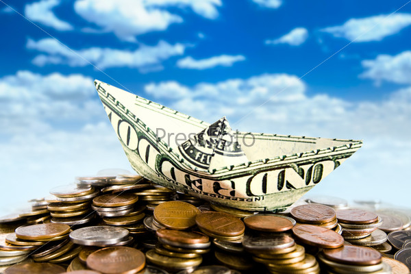 Кораблик, сделанный из долларовой банкноты, стоящий на монетах на фоне неба