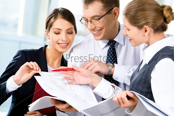Image of three happy business people looking at business plan with smiles