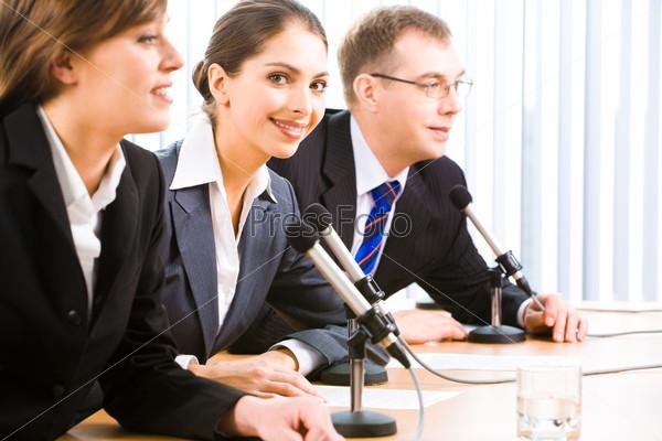 Портрет уверенных профессионалов, сидящих за столом, на котором находятся микрофоны, документы и стакан