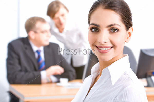 Face of beautiful employee with brown eyes on the background of her colleagues